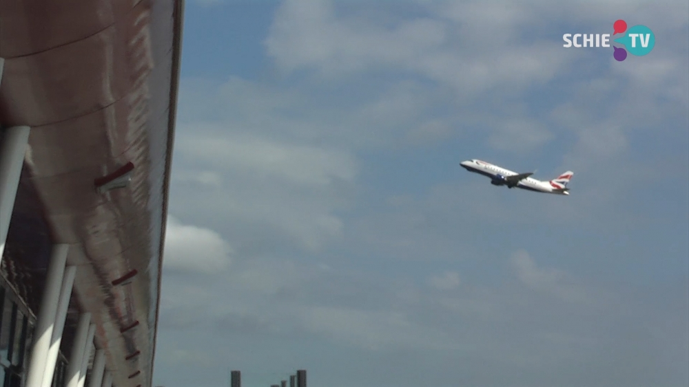 Vliegtuig komt over huizen in Schiedam